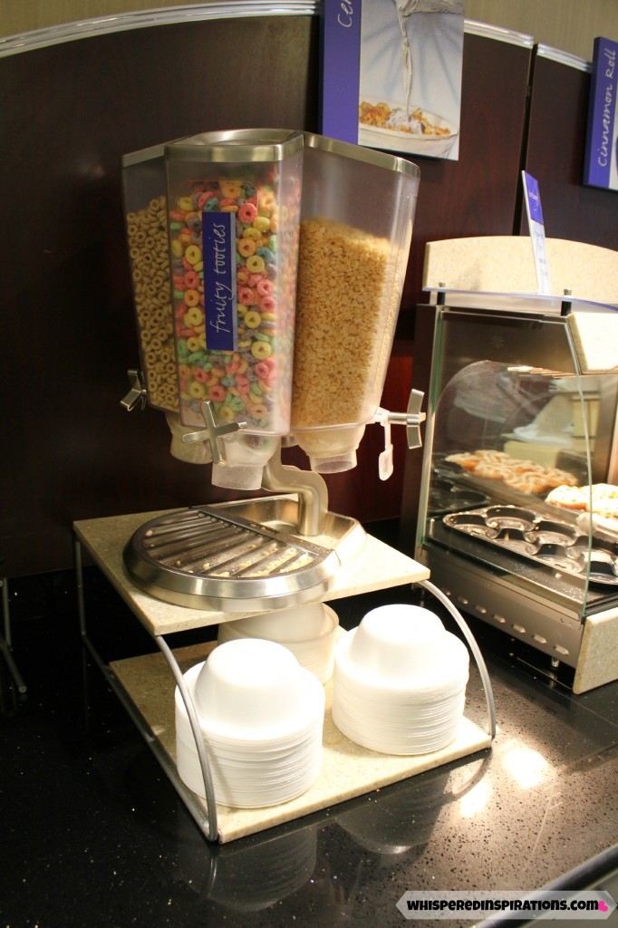 A cereal dispenser with Cheerios, Fruit Loops, and Rice Krispies at the Holiday Inn Breakfast bar.