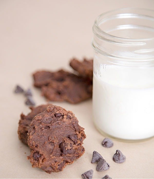 Vegan Chocolate Cookies with a mason jar of milk and chocolate chip cookies surrounding it.