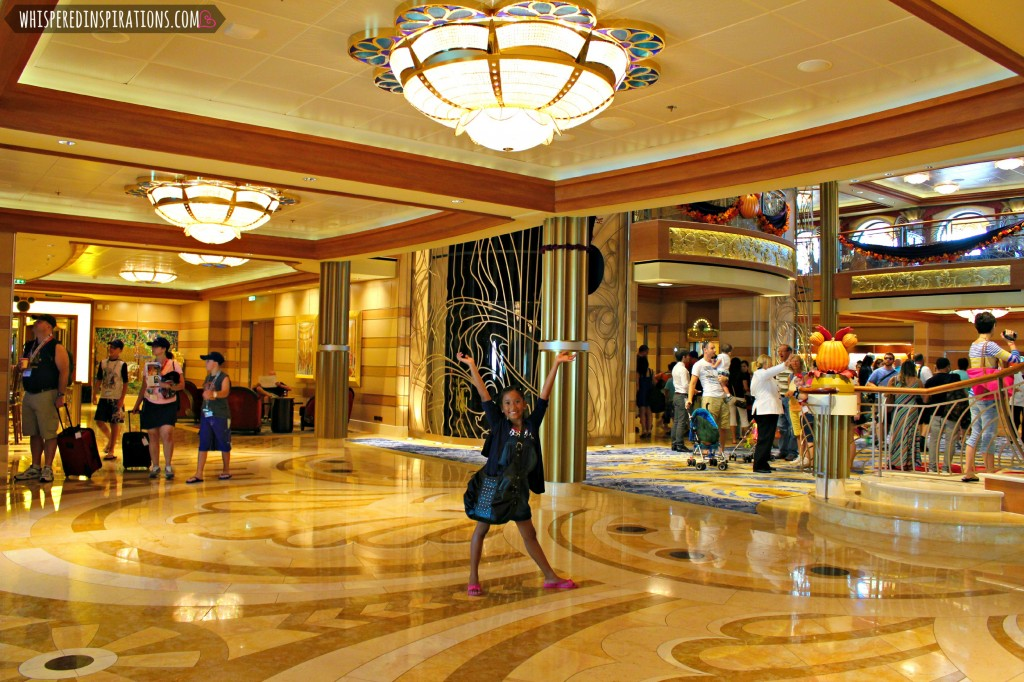 A little girl stands in the Disney Dream and holds her hands up in the air. The lobby is visible in the background.