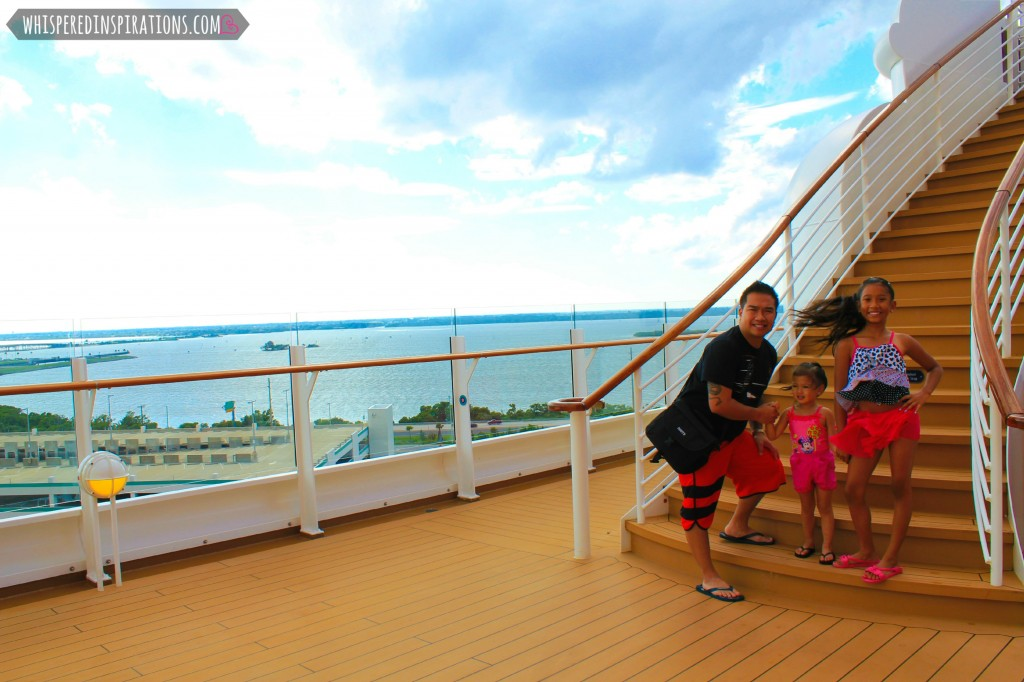 The girls stand on a staircase aboard the Disney Dream with their dad.