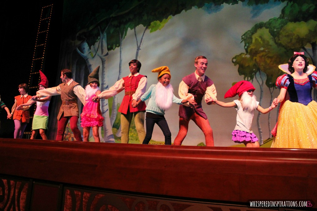 Kids dance with Snow White and dwarves on stage aboard the Disney Dream.