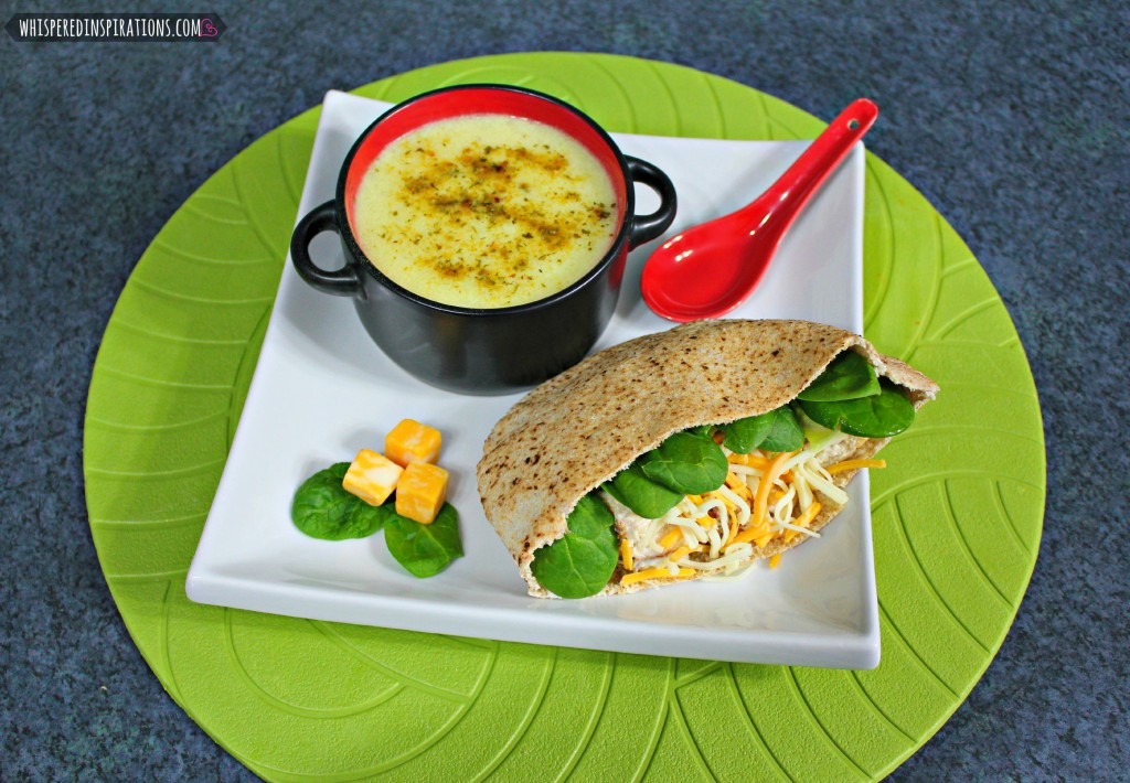 Chicken salad pita and potato soup are shown on a plate.