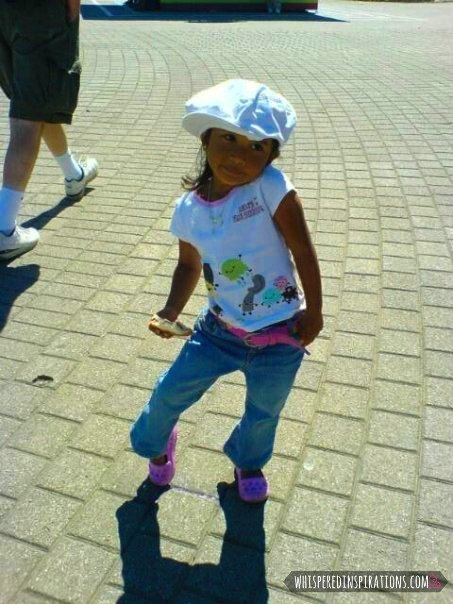 A little girl poses in a fashionable outfit.
