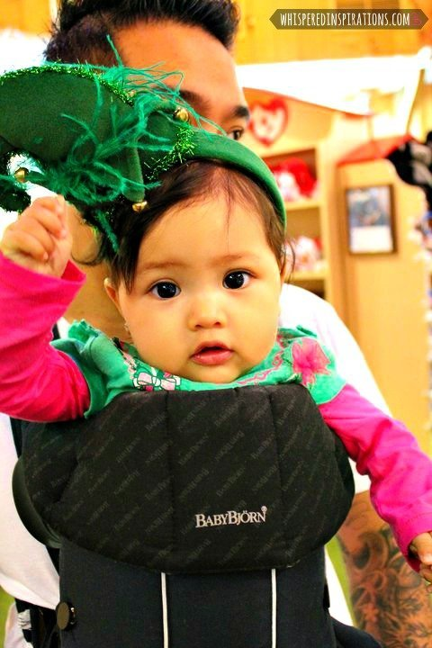 Little girl in a Baby Bjorn whilst wearing an elf headband.