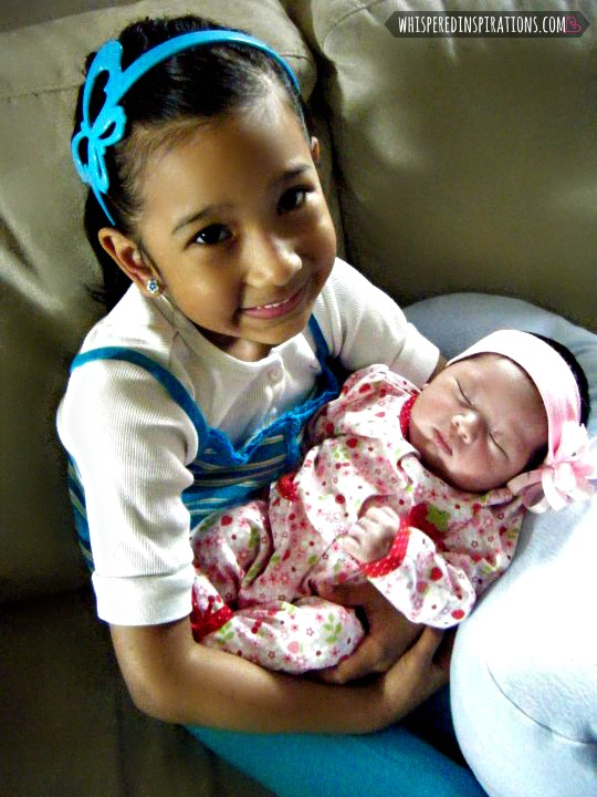 A little girl holds her infant sister.