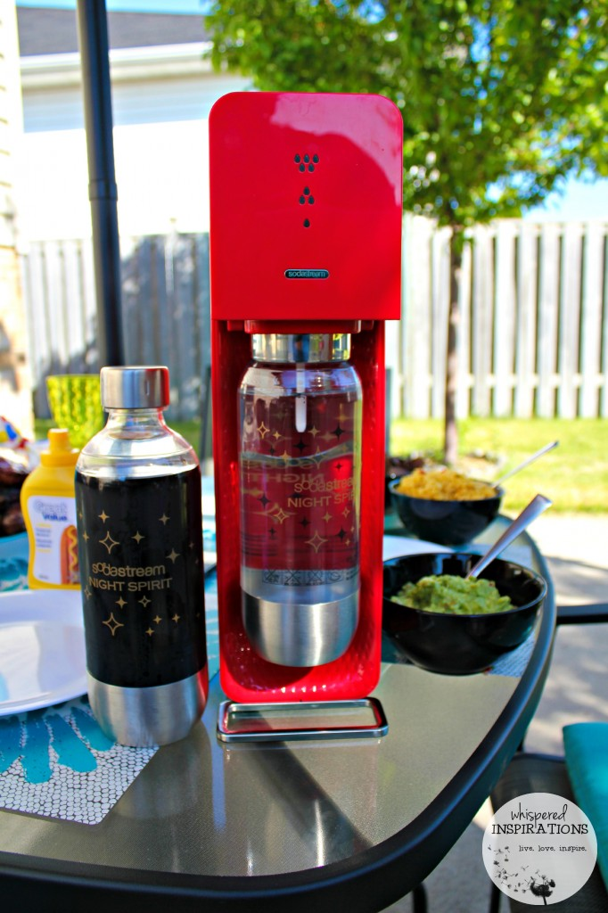 Red SodaStream is on a patio table. Rice and guacamole with a bottle of prepared soda are shown.