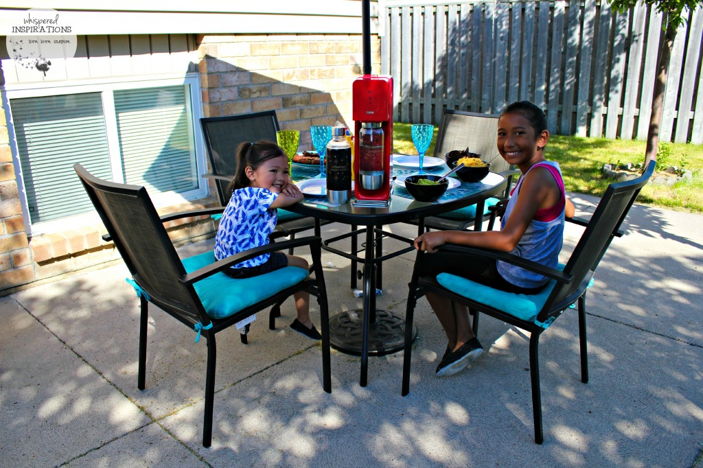 Two little girls await their BBQ meal while sipping on SodaStream sodas.