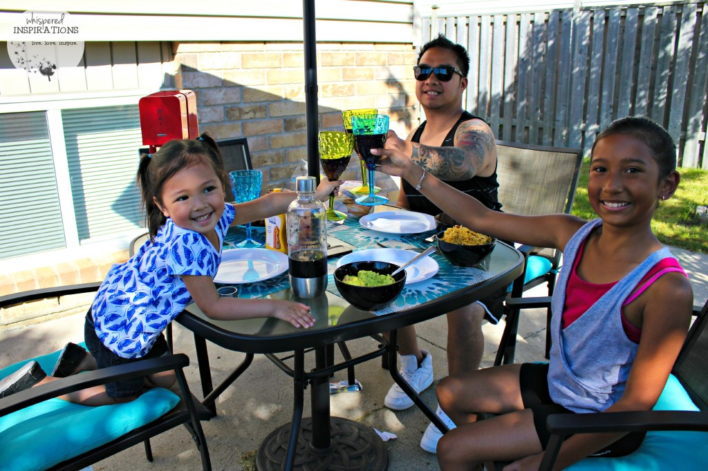 Two girls with their father cheer with SodaStream soda in their backyard patio.
