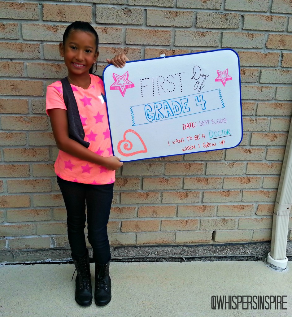Little girl holds up board on first day of school.