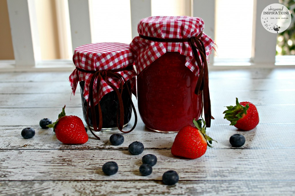 Two jars of homemade jam are wrapped with plaid and surrounded by strawberries and blueberries. Made with Bernardin Home Canning.