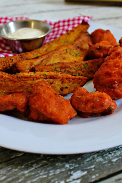 Wedges served on a plate with blue cheese and wings.
