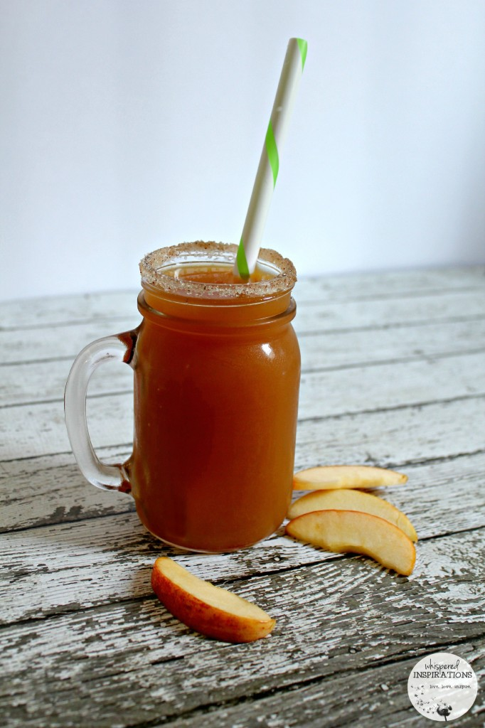 A Bernardin mason jar rimmed with sugar and cinnamon filled with apple cider and a large straw.
