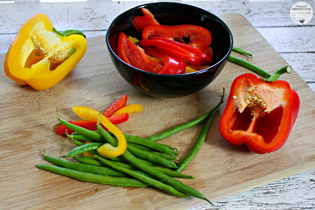 Red and yellow pepper are cute and green beans are strewn on a cutting board.