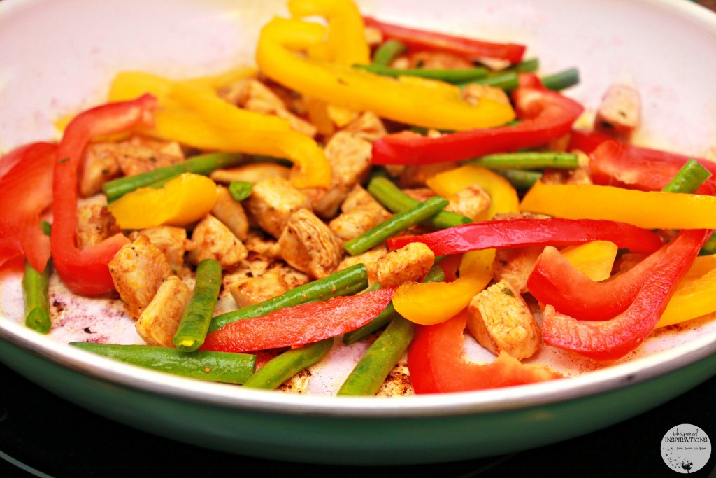 Skillet with red and yellow pepper, and green beans cook.