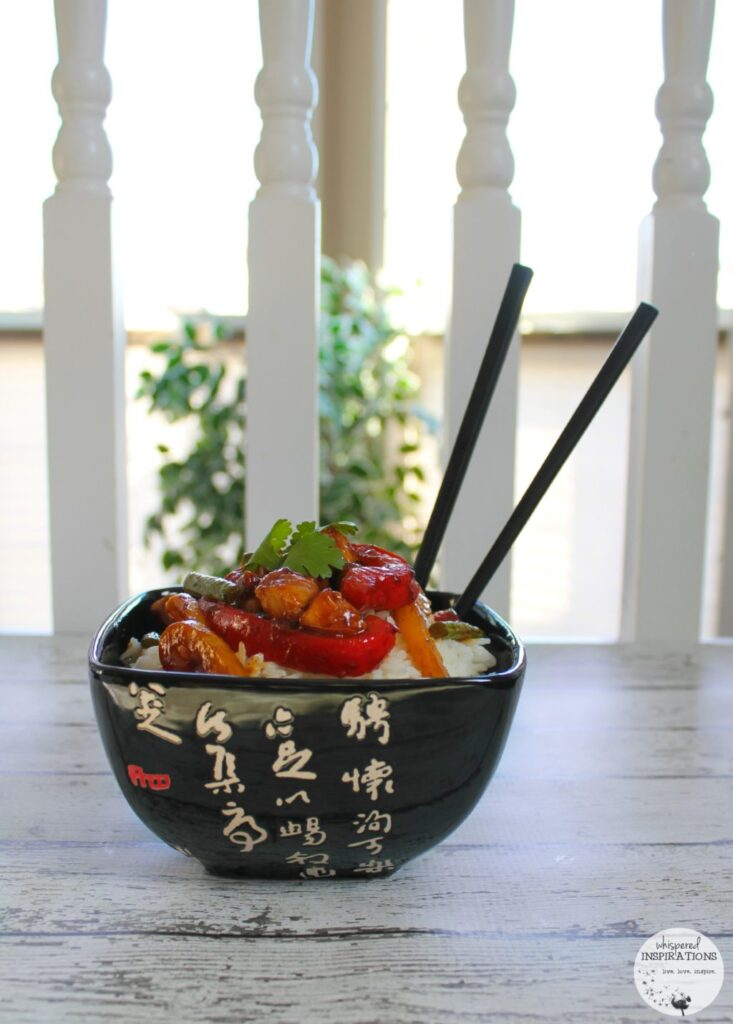 A bowl with rice and Sesame Chicken Stir-Fry and chop sticks.