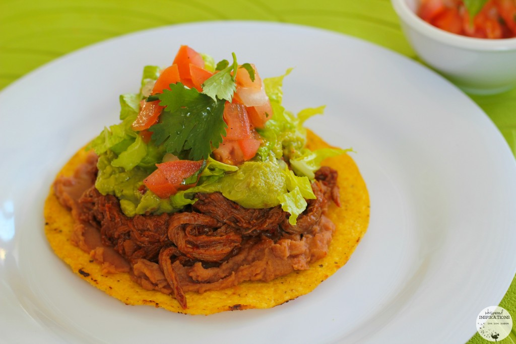 A Salvadorean Beef Enchilada topped with refried beans, shredded beef, guacamole, pico de gallo, and lettuce.