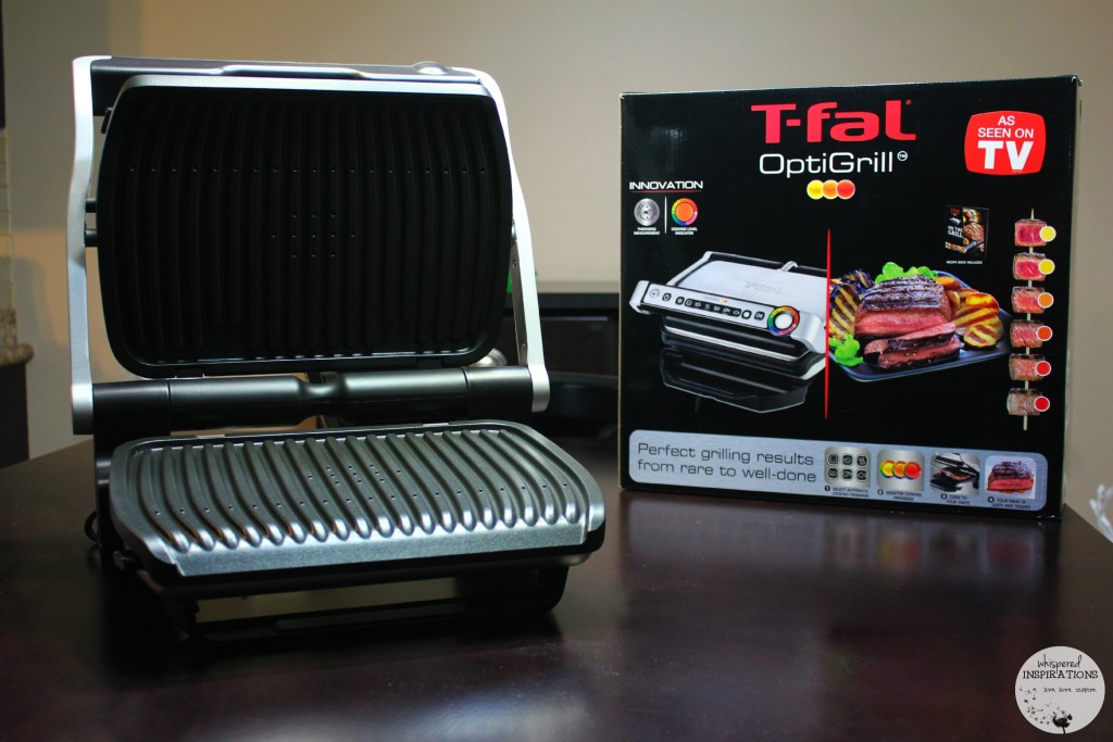 The T-fal Optigrill is displayed open on a kitchen table.