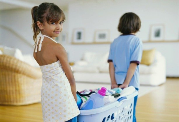 Girl (6-8) carrying basket of laundry with brother (5-7) smiling