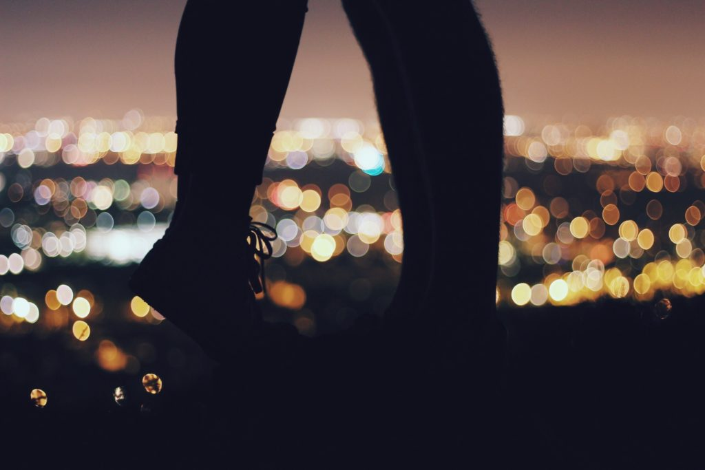 A couples' feet are shown and the girl is on her toes, the city lights are in the background.