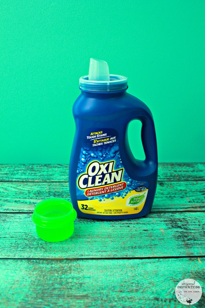 One of the top baby and child products. A bottle of OxiClean with a lid full of the clear liquid.
