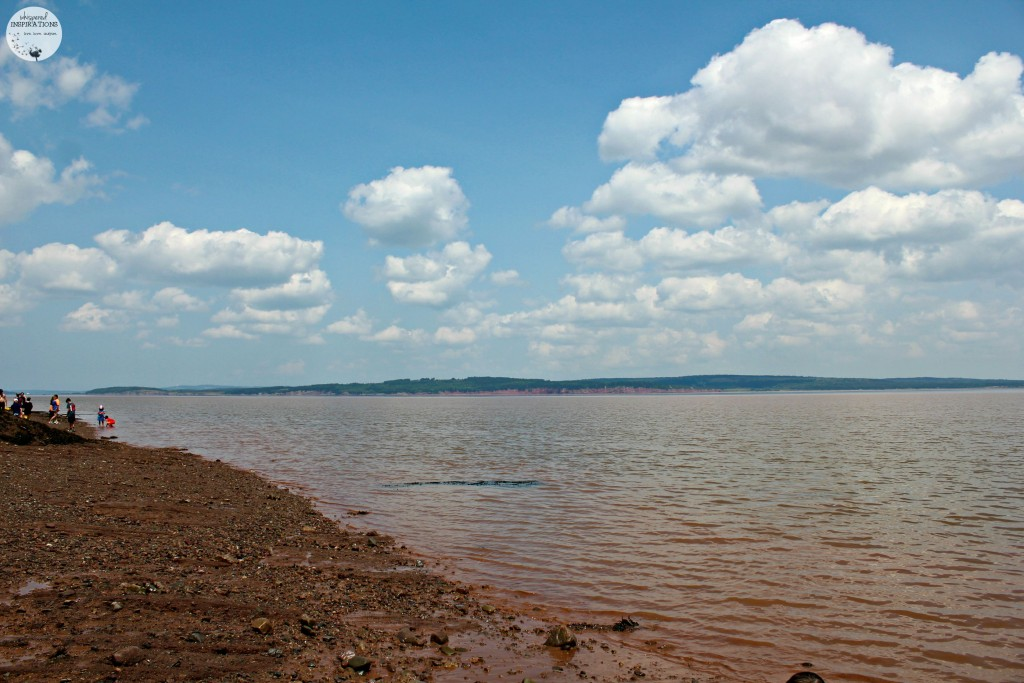 A beautiful sky is mirrored in the orangey-clay waters of the Bay of Fundy at low tide.
