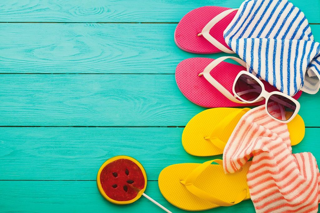 Yellow and Pink flipflops, striped towels and sunglasses adorn a teal floor.