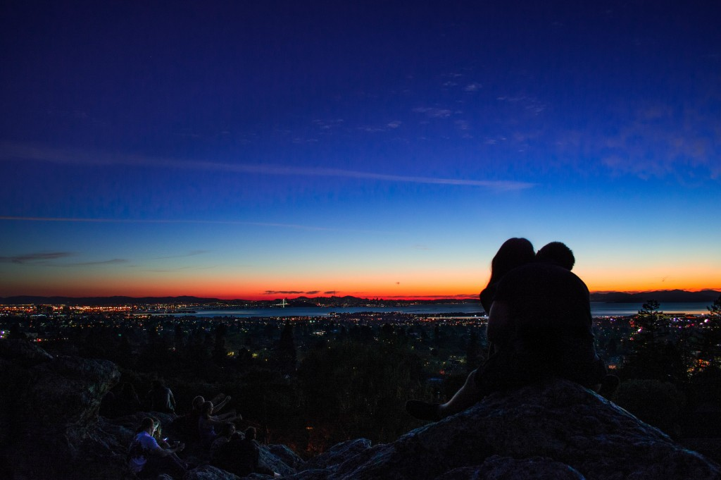 A couple embrace while they overlook the city at night. Keep the spark alive.