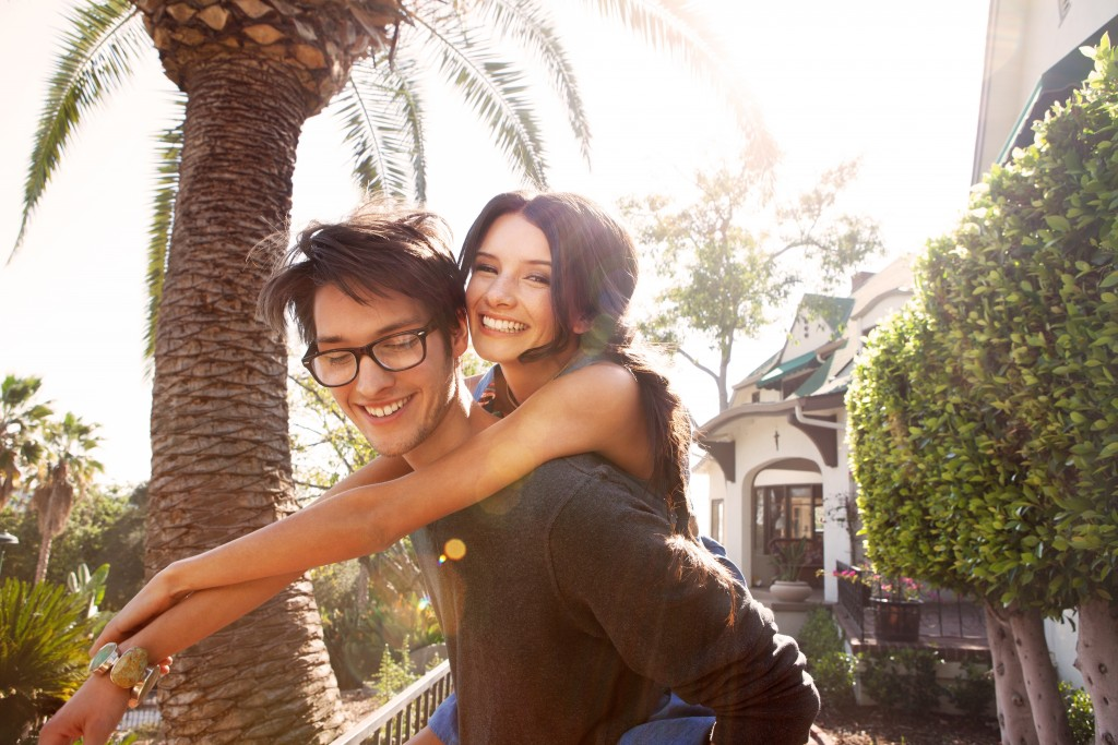 A girl rides piggyback on boyfriend. Cheap date ideas!