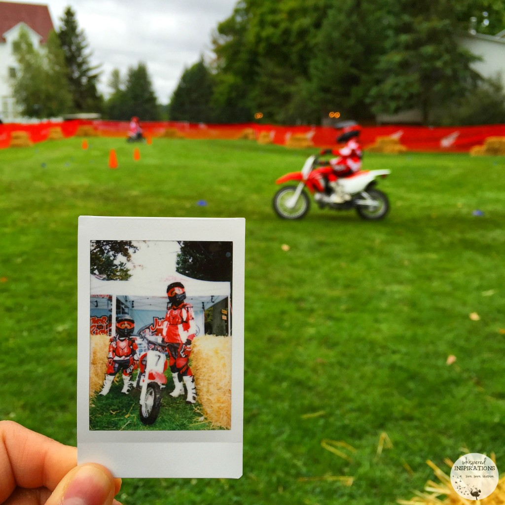 A Poloroid is held up against a picture of Gabby riding on a dirt bike. Gabby is blurred in the background riding the dirt bike.