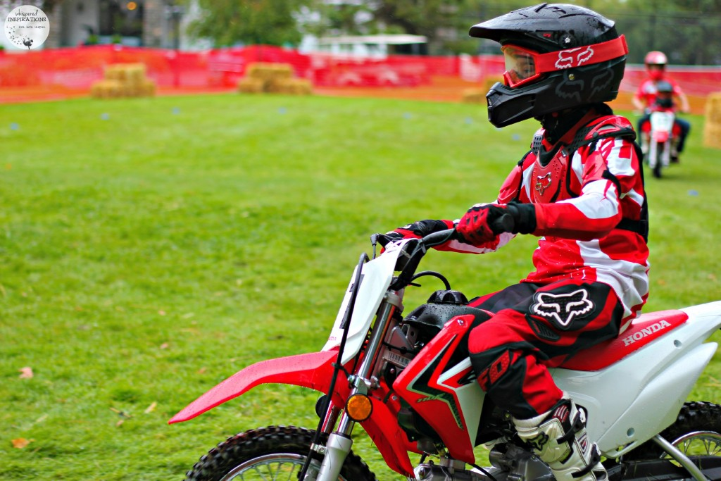 Gabby riding on a dirt bike with helmet and full riding gear on.