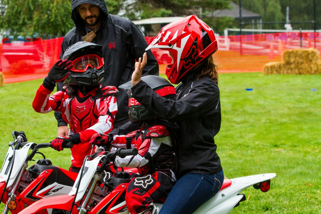 Gabby and Mimi ride on dirt bikes. Mimi is riding with a grown-up.