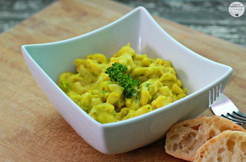 A bowl of guacamole macaroni and cheese is served with bread.