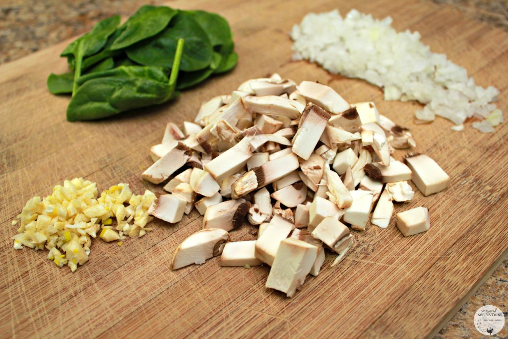 Chopped garlic, mushrooms, onions, and spinach are on chopping block.