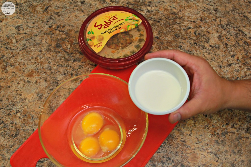Cream being added to eggs with Sabra hummus on the side.