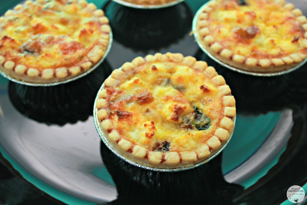 Mini quiches are on a plate, they are golden brown and delicious.