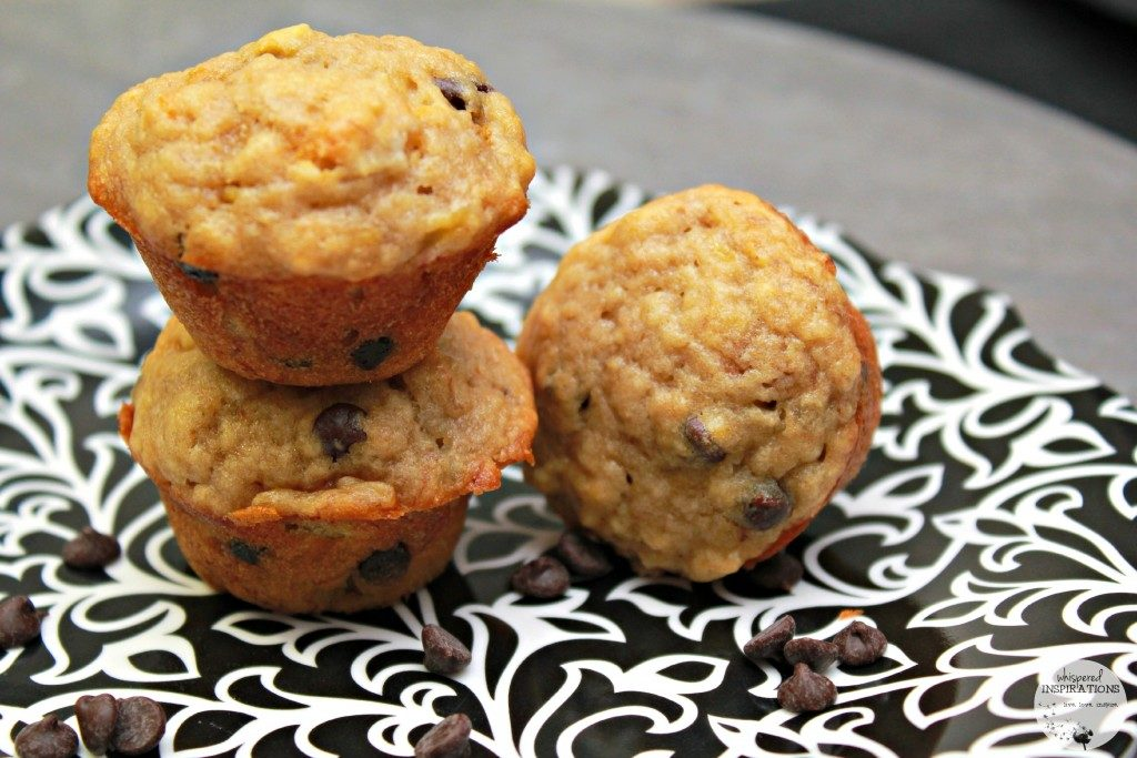 Mini banana chocolate chip muffins are stacked on a plate.