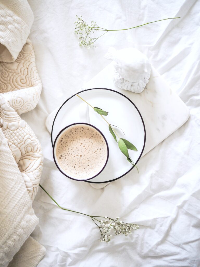 Bed with latte and plate, white sheets, and a blanket.