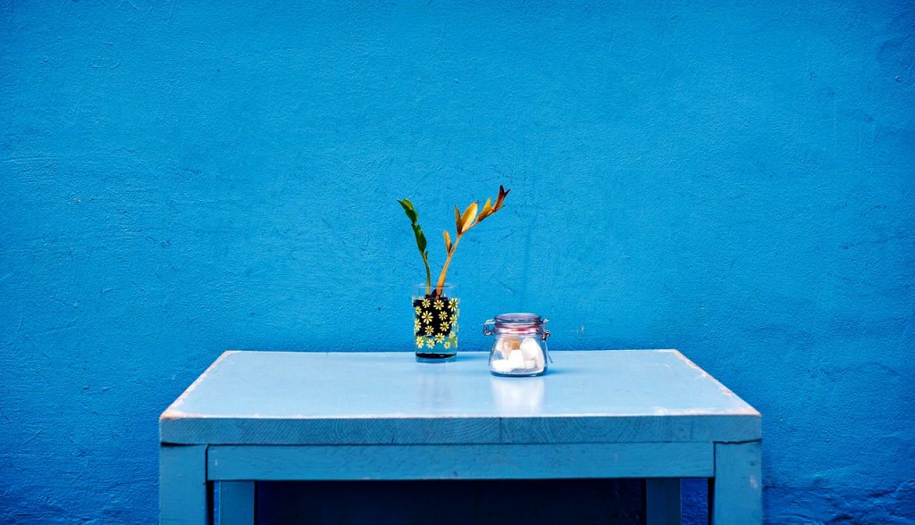 A bright blue wall with a blue table and plant and jar.