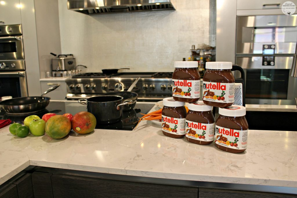A chef's kitchen with fruit and five jars of Nutella.
