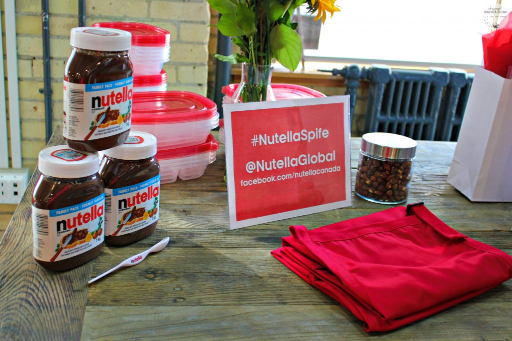 Nutella jars, Nutella spife, and aprons on a table.