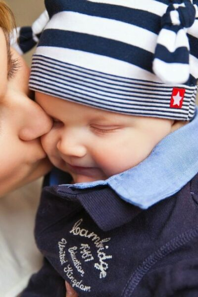 A mother kisses her son on the cheek.
