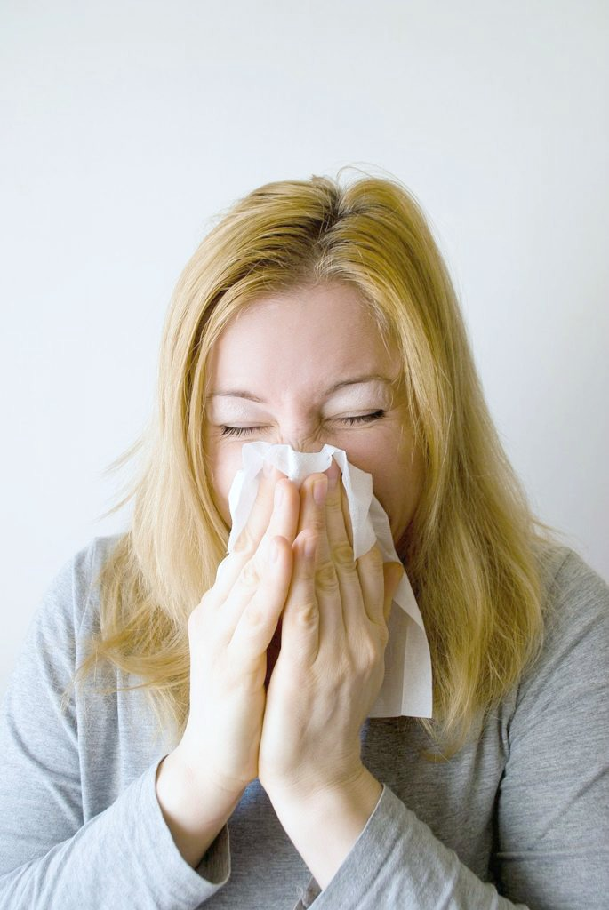 Woman sneezing into a tissue. Her eyes are closed.