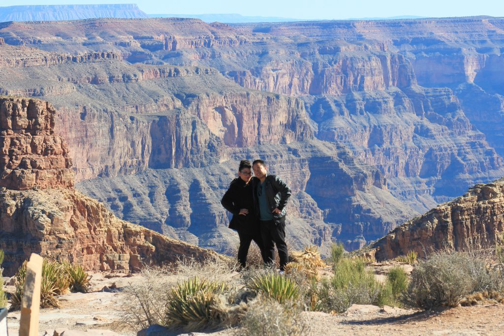 The Grand Canyon is pictured in the background and Nancy and Darasak stand at the edge of the Grand Canyon.