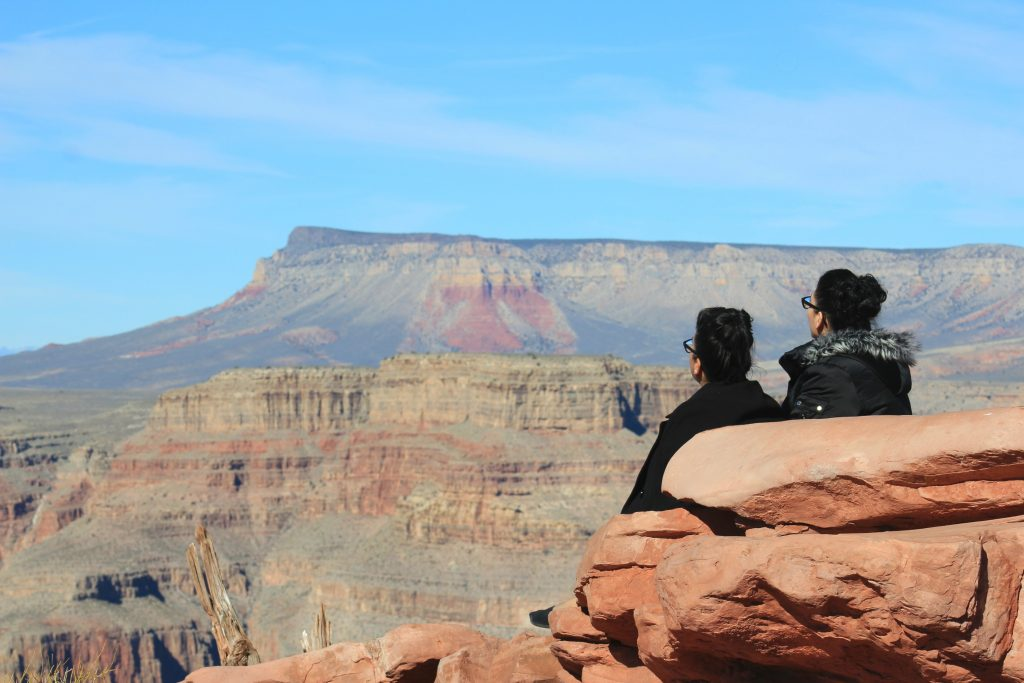 Nancy and Susana sit on the edge of the Grand Canyon watching the birds fly by.
