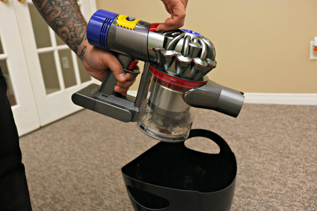Emptying the Dyson V8 Absolute into a trash bin.