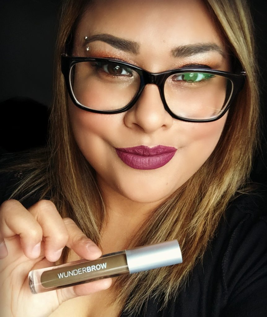 Nancy wearing Morphe eyeshadows and holding a tube of Wunderbrow.