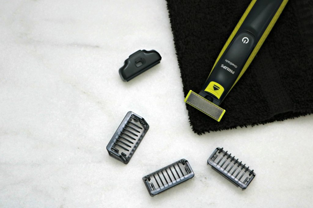 A Philips One Blade on a black towel, with the replacement blades.