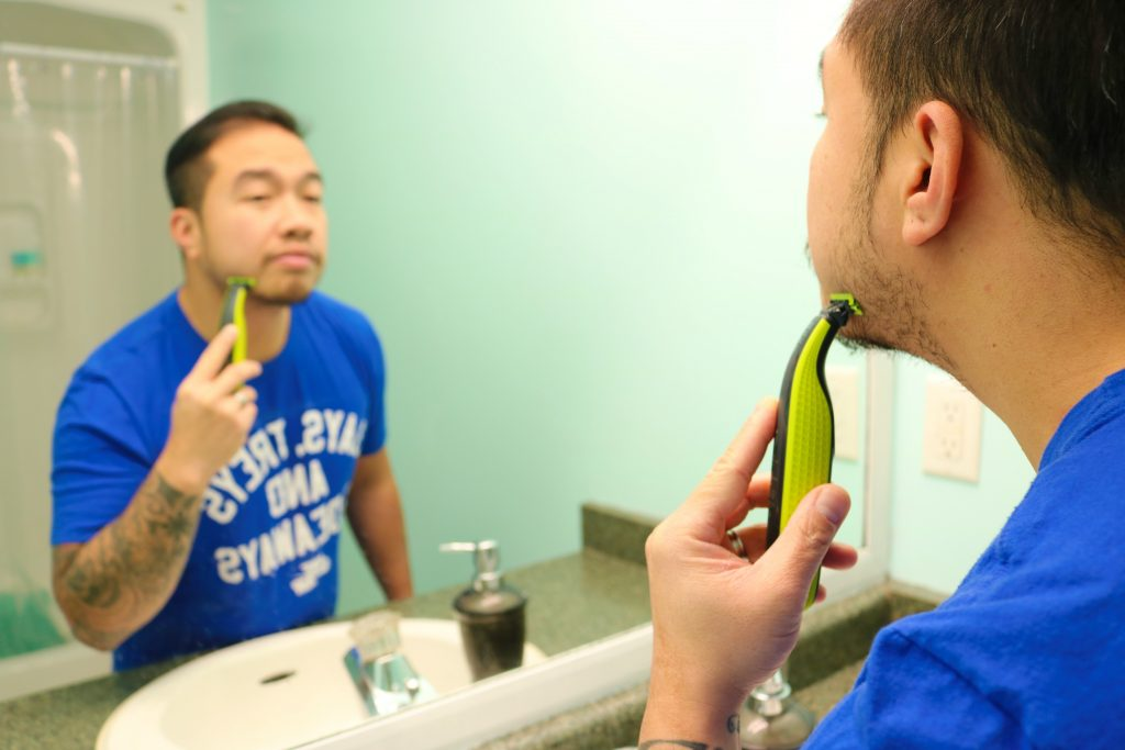 Darasak shaving his face in front of mirror. He is using the Philips One Blade.