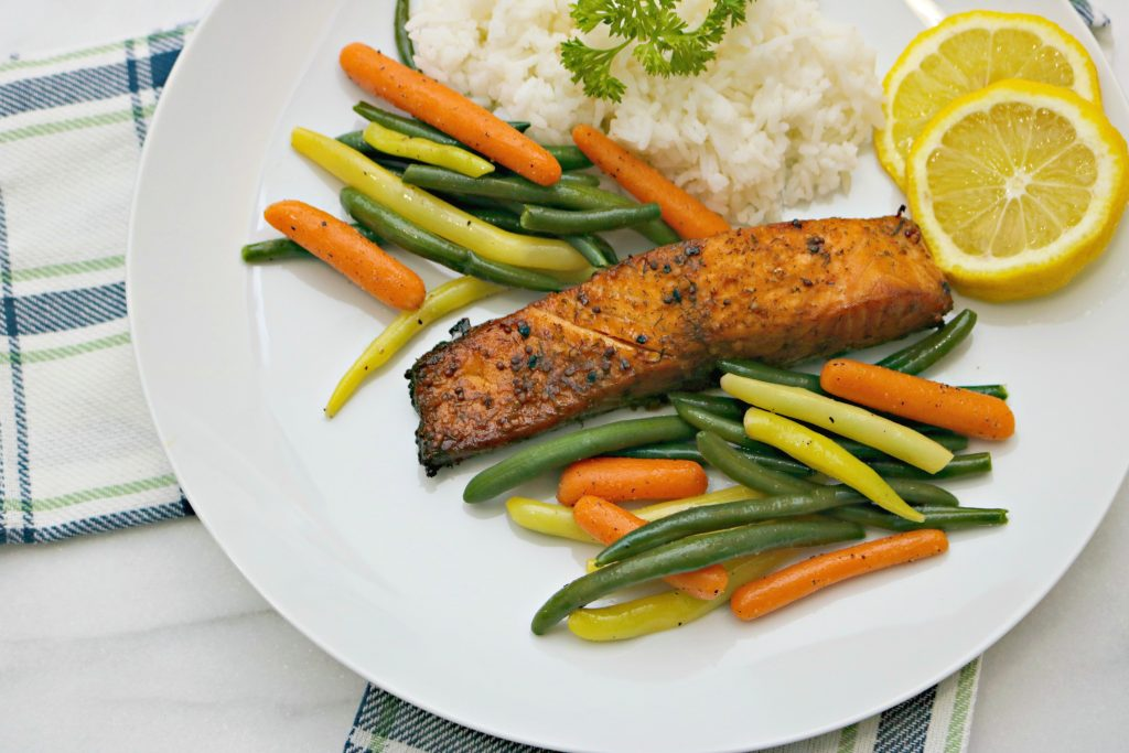 A charbroiled fish is served with green and yellow beans, carrots, and a bed of white rice with lemon.