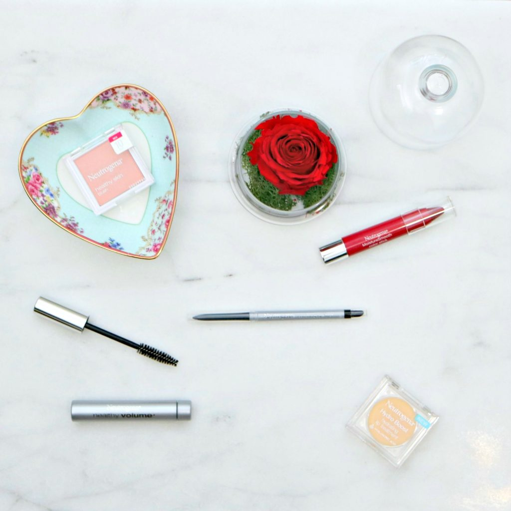 A beautiful Royal Albert dish, a rose in a glass container, and Neutrogena makeup. Lip gloss, mascara, eyeliner, lip tint, and blush.